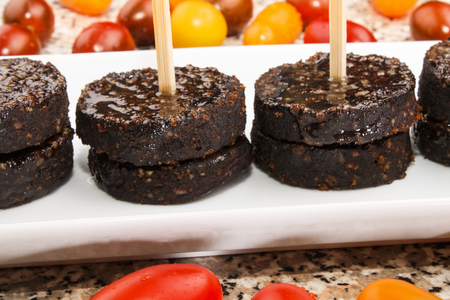 irish black pudding as party snack on a white plate and tomato in the background