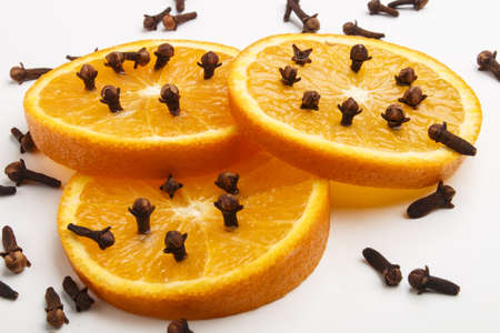 fresh and juicy orange slices peppered with spice cloves Stock Photo