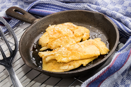 scrambled egg and salt in an old cast iron pan Stock Photo