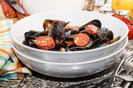 warm spanish mussel soup with sliced chorizo and tomato sauce Stock Photo