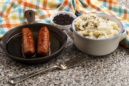 peppered mashed potato in a bowl and grilled british sausages in a small cast iron pan Stock Photo
