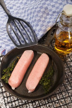 home made raw british sausages with herbs in a cast iron pan Reklamní fotografie