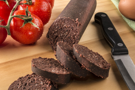 raw sliced irish black pudding on a wooden board