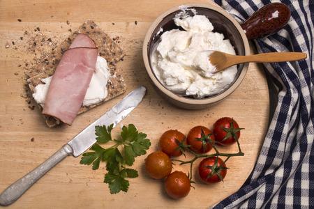 healthy breakfast with crispbread, quark, parsley and smoked ham on a wooden board Standard-Bild