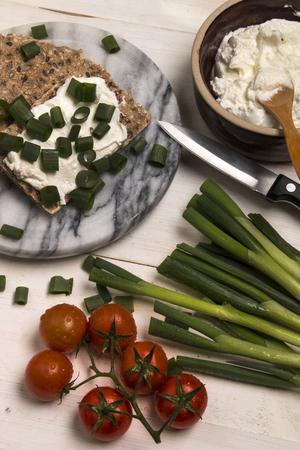 healthy, vegetarian breakfast with crispbread, quark and fresh spring onion on marble