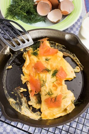 omelette with scotch smoked wild salmon in a cast iron pan Standard-Bild