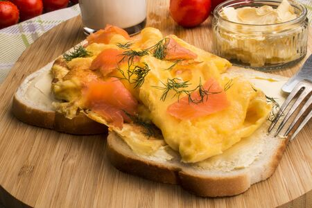 omelette with smoked salmon on toast, tomato, horseradish, a glass of milk and a fork