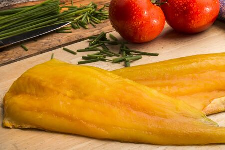 smoked haddock fillet on a wooden board, fresh tomato and chive in the background