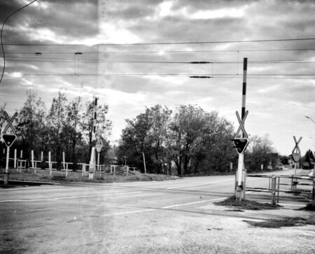 Railway crossing and empty road - This black and white camera obscura photo is NOT sharp due to camera characteristic. Taken with a professional pinhole camera Standard-Bild