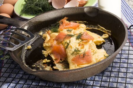 Scrambled eggs with salmon and dill in a cast iron pan Standard-Bild