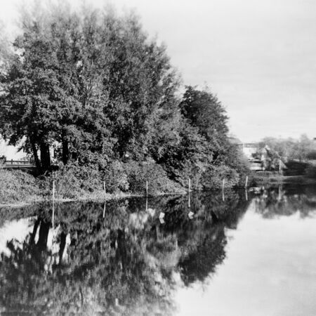 Reflection of trees in the water- This black and white photo is NOT sharp due to camera characteristic. Taken on film with a medium format camera Standard-Bild