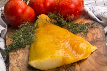 smoked scottish haddock on a wooden board with fresh tomato