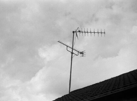 old radio and television antenna on a house roof, this black and white photo was taken with a pinhole film camera, which corresponds to the camera characteristic