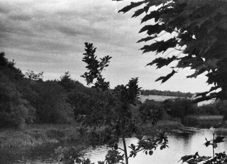 the river and many trees on the sides, this black and white photo was taken with a pinhole film camera, which corresponds to the camera characteristic Standard-Bild