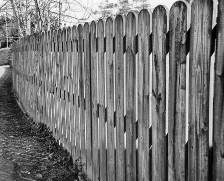 self made fence from wooden slats, this picture was taken on old fashion black and white film Standard-Bild