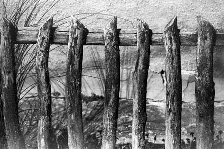 old, rustic, self made fence made of wood - this picture was taken with an old analog camera and black and white film