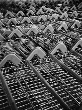 Metal supermarket shopping trolley with plastic handle. This black and white picture was taken with an analog medium format camera