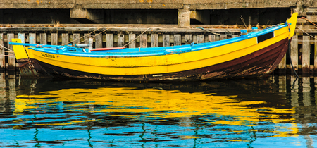 old yellow boat moored in the port