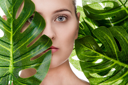 Woman beauty portrait with tropical leaf Imagens