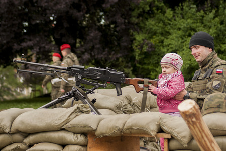 Szczecin, Poland - Mai 29, 2014  Veterans Day in Poland  Unidentified soldier with his daughter Child holds the hand machine gun