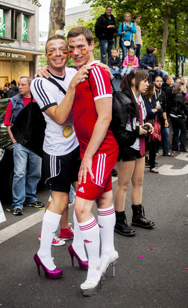 BERLIN, GERMANY - JUNE 21, 2014 Christopher Street Day Elaborately dressed people participate in the parade celebrates gays, lesbians, bisexuals and transgenders Prominent in the image are a gay couple in heels, dressed as football players