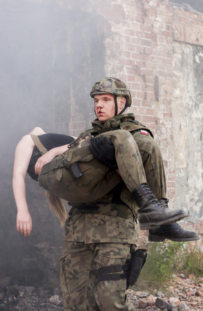 shot: SZCZECIN, POLAND - MAY 31, 2014: Wounded Woman and Soldier in Polish Army Uniform during  Historical reenactment Editorial