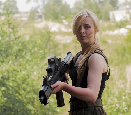 wounded: SZCZECIN, POLAND - MAY 31, 2014: Beautiful sexy blond woman holding army weapon, during historical reconstruction
