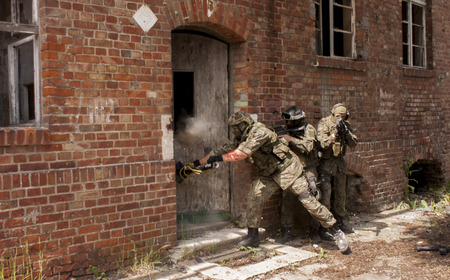 stormed: SZCZECIN, POLAND - MAY 31, 2014: Three soldiers in full uniform stormed the building, during historical reconstruction