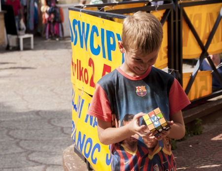MIEDZYZDROJE, POLAND - JULY 20, 2014: Smiling yung boy trying to solve an intelligence Rubik