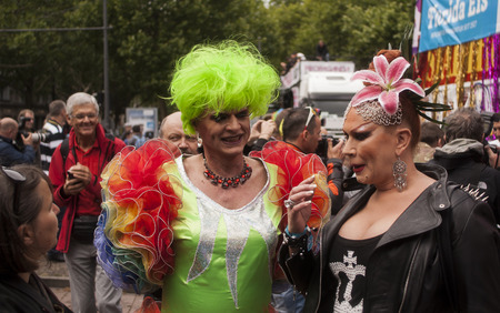 BERLIN, GERMANY - JUNE 21, 2014: Christopher Street Day. Crowd of people Participate in the parade celebrates gays, lesbians, bisexuals and transgenders. Prominent in the image, elaborately dressed participants.
