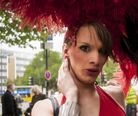 bisexuals: BERLIN, GERMANY - JUNE 21, 2014: Christopher Street Day. Crowd of people Participate in the parade celebrates gays, lesbians, bisexuals and transgenders. Prominent in the image, elaborately dressed participant.