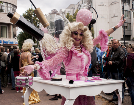 BERLIN, GERMANY - JUNE 21, 2014: Christopher Street Day. Crowd of people Participate in the parade celebrates gays, lesbians, bisexuals and transgenders. Prominent in the image, elaborately dressed participant woman.