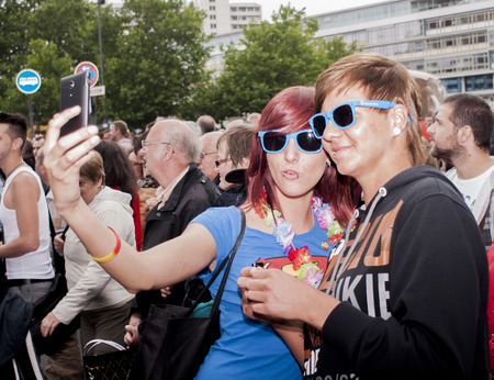 BERLIN, GERMANY - JUNE 21, 2014: Christopher Street Day. Crowd of people Participate in the parade celebrates gays, lesbians, bisexuals and transgenders. Prominent in the image, elaborately dressed participants taking selfie Editorial