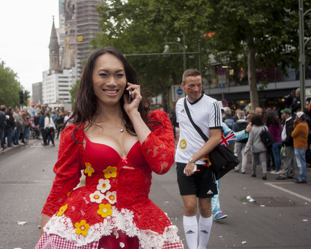 bisexuals: BERLIN, GERMANY - JUNE 21, 2014: Christopher Street Day. Crowd of people Participate in the parade celebrates gays, lesbians, bisexuals and transgenders. Prominent in the image, elaborately dressed participant talk on the phone Editorial