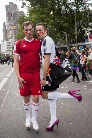 bisexuals: BERLIN, GERMANY - JUNE 21, 2014:Christopher Street Day. Elaborately dressed people participate in the parade celebrates gays, lesbians, bisexuals and transgenders. Prominent in the image are a gay couple in heels, dressed as football players.