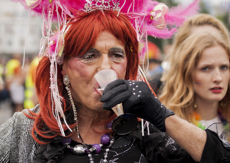 bisexuals: BERLIN, GERMANY - JUNE 21, 2014: Christopher Street Day. Crowd of people Participate in the parade celebrates gays, lesbians, bisexuals and transgenders. Prominent in the image, elaborately dressed participant drinking shampain