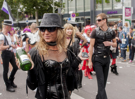 bisexuals: BERLIN, GERMANY - JUNE 21, 2014: Christopher Street Day. Crowd of people Participate in the parade celebrates gays, lesbians, bisexuals and transgenders. Prominent in the image, Elaborately dressed woman with bottle of champagne