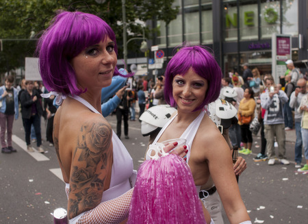 bisexuals: BERLIN, GERMANY - JUNE 21, 2014: Christopher Street Day. Crowd of people Participate in the parade celebrates gays, lesbians, bisexuals and transgenders. Prominent in the image, elaborately dressed girls