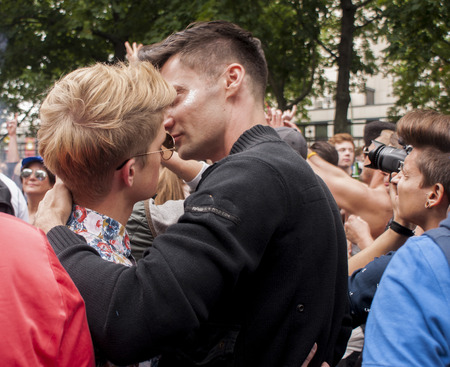 bisexuals: BERLIN, GERMANY - JUNE 21, 2014:Christopher Street Day.Unidentified gay couple cuddling during Gay pride parade.Crowd of people participate in the parade celebrates gays, lesbians, bisexuals and transgenders.