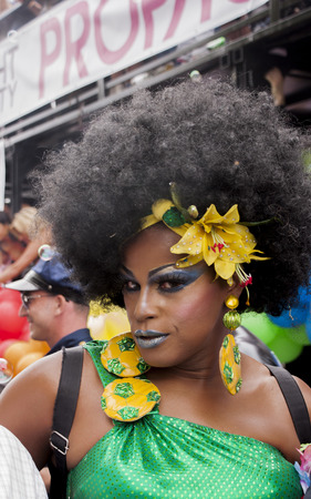 bisexuals: BERLIN, GERMANY - JUNE 21, 2014: Christopher Street Day.Crowd of people Participate in the parade celebrates gays, lesbians, bisexuals and transgenders.Prominent in the image a transgender dressed in brazilian style. Editorial