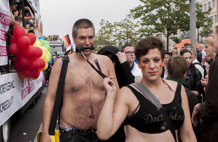 copule: BERLIN, GERMANY - JUNE 21, 2014:Christopher Street Day. Crowd of people Participate in the parade celebrates gays, lesbians, and transgenders. Prominent in the image, elaborately dressed couple.
