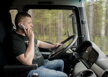 truck driver: SZCZECIN, POLAND -  APRIL 23, 2014: Truck driver driving and talking to phone
