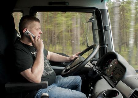 hablando por telefono: SZCZECIN, Polonia - 23 de abril 2014: Conductor de cami�n de conducci�n y habla con el tel�fono