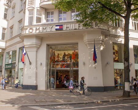 tommy: BERLIN, GERMANY - MAY 30, 2014: Pedestrians walk past a Tommy Hilfiger store. Tommy Hilfiger is an American fashion, apparel, design, fragrance retail company