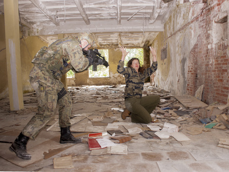 reflect: SZCZECIN, POLAND - MAY 31, 2014: Female hostage and soldier with gun, during historical reconstruction