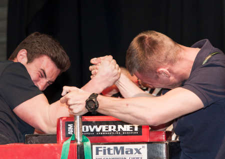 down beat: Szczecin, Poland - April 12, 2015:  Unidentified sportsmen compete in arm wrestling