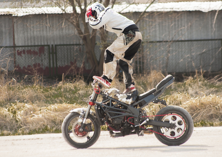 speeder: Szczecin, Poland - April 11, 2015: Stuntman riding a motorcycle standing.