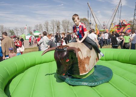 Chrzypsko, Poland - May 03, 2015: Unidentified boy playing bull riding toy