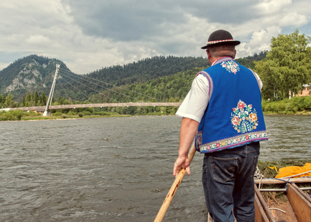 rafter: DUNAJEC RIVER, POLAND - JUNE 26, 2015: Raftsman rafts tourists on the Dunajec river, south of Poland. The rafting near the slovakian border is very popular tourist attraction. Editorial
