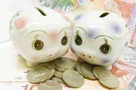 two piggy bank with notes and coins photo